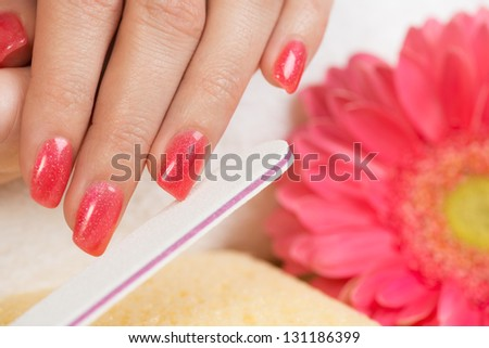 Manicure treatment. Close up of female hands having manicure. Very nice pink nail polish on fingernails. Selective focus. - stock photo