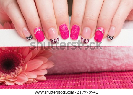Manicure treatment. Close up of female hands holding nail file. Very interesting nail art on fingernails.  - stock photo