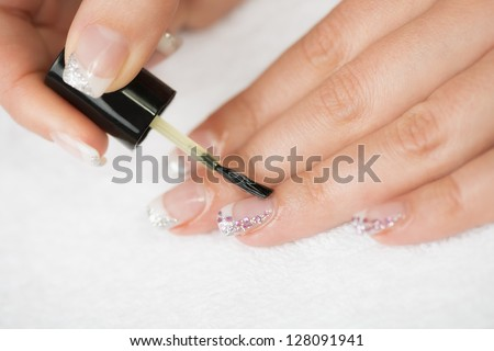 Manicure treatment - Manicure treatment, applying cuticle oil on woman nails. - stock photo
