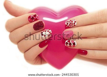 Manicure with rhinestones in the shape of hearts and pink balls on white and red nail Polish on a white background. - stock photo