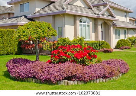 Manicured House and Garden displaying annual and perennial gardens in full bloom. - stock photo