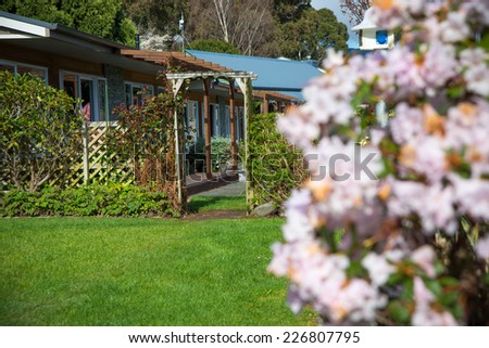 Manicured House and Garden displaying annual and perennial gardens in full bloom - stock photo
