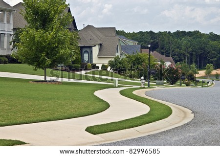 Manicured lawns and curving sidewalks in a modern neighborhood.
