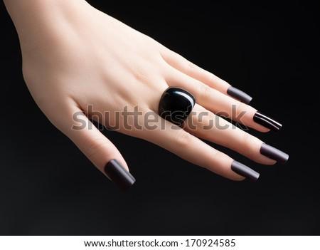 Manicured Nail with Black Matte Nail Polish. Fashion Manicure. Long Nails with Dark Nailpolish isolated on Black Background. Salon. Nail Art. Black Ring - stock photo