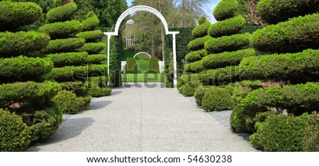 Manicured shrubs line an estate entrance. - stock photo