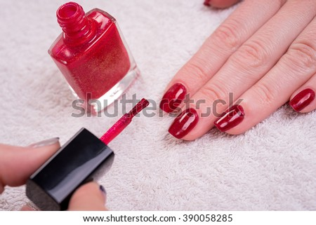 manicured woman's nails with red nail polish on white towel - stock photo