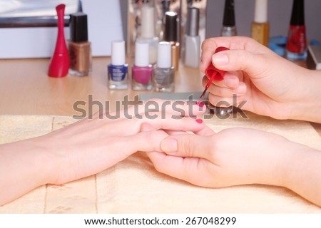 Manicurist doing manicure client painting nails with red nail polish in salon on yellow towel  - stock photo