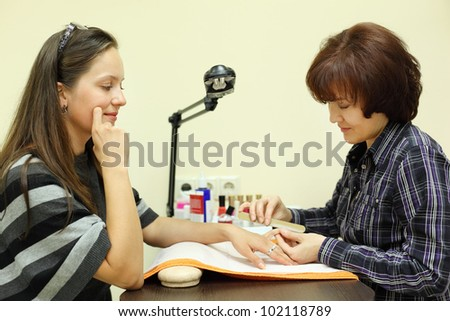 Manicurist makes manicure by nailfile for woman in beauty salon; focus on client - stock photo