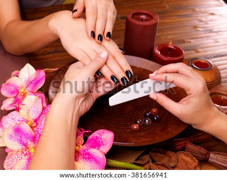 Manicurist master  makes manicure on woman's hands - Spa treatment concept - stock photo