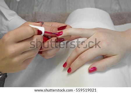 Manicurist, nail paint red color to the girl client  at beauty salon.