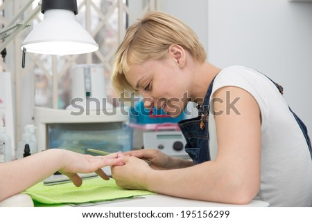 manicurist  sawing client nails - stock photo
