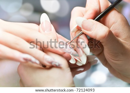 Manicurist treating client at beauty salon. Manicure stage: Painting on the nail - stock photo