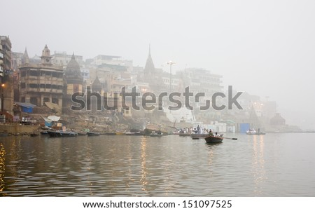 manikarnika ghat in the mist, ganga river, varanasi india. - stock photo
