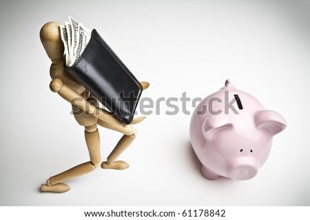 Manikin carrying a wallet full of money towards a piggy bank - stock photo