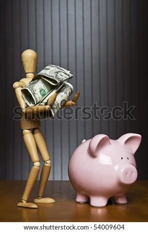 Manikin carrying money towards a piggy bank - stock photo