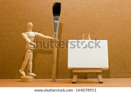 manikin, paint brush and easel.