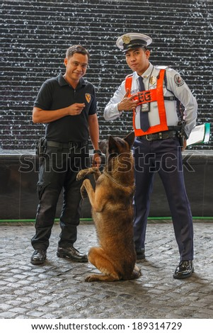 MANILA - FEB 12: Unidentified security guards with dog at Diamond Hotel on 12 Feb, 14 in Manila. It is estimated 3.7 million of security guards including doormen in the Philippines.