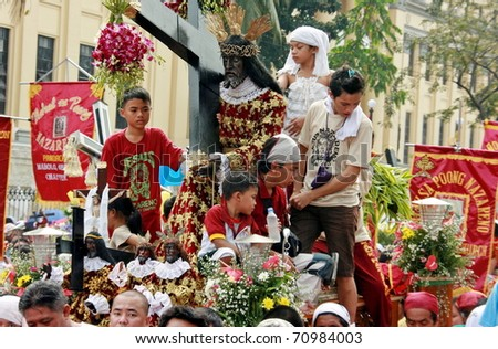 MANILA - JAN. 9: Devotees celebrate the feast of The Black Nazarene on January 9, 2011 in Manila Philippines. The fiesta celebrated by hundred thousand devotees parading the image in the city. - stock photo
