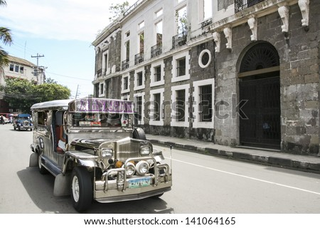 MANILA - JULY 10: jeepney public transport driving past derelict building in intramuros on 10 July 2009 in manila. Jeepneys are the most popular means of public transportation in the Philippines. - stock photo