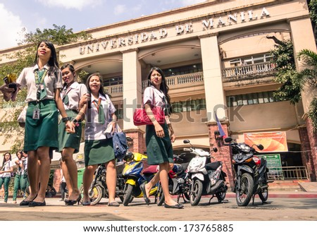"MANILA, PHILIPPINES - 29 JANUARY, 2014: young female students going out from ""Universidad de Manila"". The main campus of the public university is at the heart of the city near LRT Central Terminal. - stock photo"