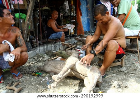 MANILA, PHILIPPINES - JUNE 22, 2015: Wood carvers puts finishing touches on an ornamental figurine sold at a flea market called Dapitan Arcade.