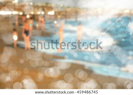 manipulated blurry background image of people on beach