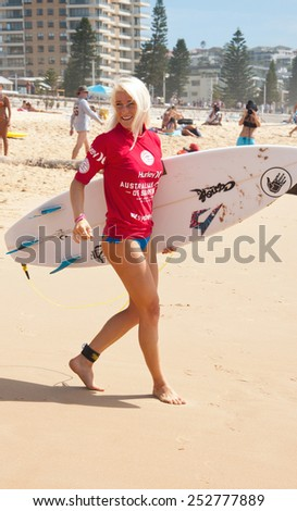MANLY AUSTRALIA - FEBRUARY 15: Tatiana Weston-Webb headng towards water in quarter finsl of competition among women in the Australian Surfing Open at Manly Beach. February 15, 2015 Manly, Australia.  - stock photo