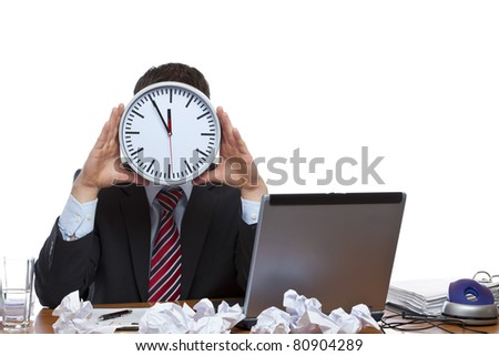 Mann under extreme time pressure holds clock in front of face. Isolated on white background.