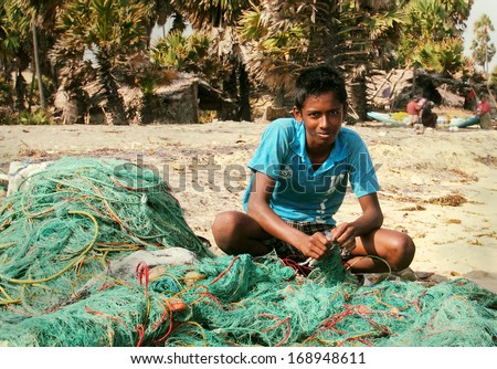 MANNAR/SRI LANKA - FEB 01: Unidentified young Tamil fisherman repairs fish nets after morning fishing on February 01, 2013 in Mannar island, Sri Lanka, South Asia. - stock photo