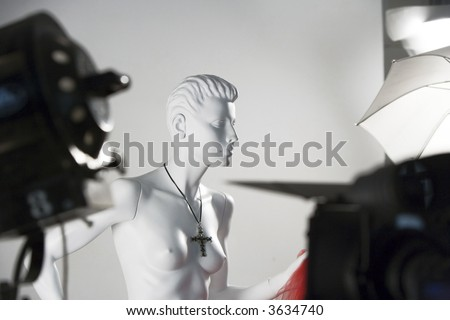 Mannequin at a photo session with lightning gear background - stock photo