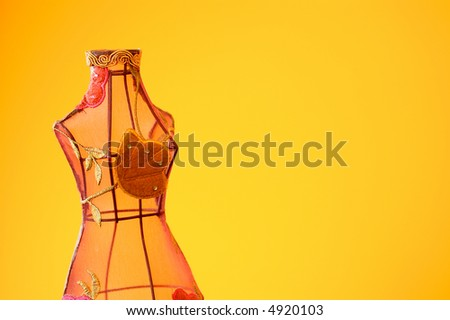 Mannequin made of wire and clothes on warm background. - stock photo
