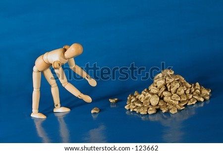 Mannequin reaching for gold nuggets.  Metaphor. - stock photo