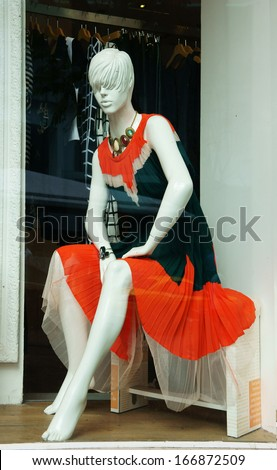 Mannequin wear stylish clothes and necklace showed on shopwindow of fashion shop - stock photo