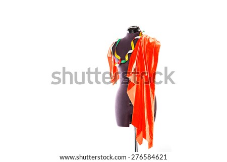 Mannequin with a piece of red cloth and a measuring tape. The concept of fashion and fashion design. - stock photo
