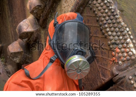Mannequin with orange protective suit and gas mask - stock photo