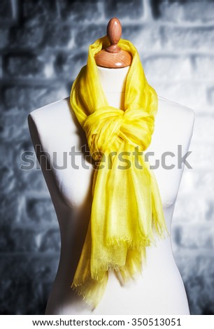 Mannequin with silk cloth. Knitted fashion yellow organza shawl on tailor bust. Single object with clipping path  - stock photo