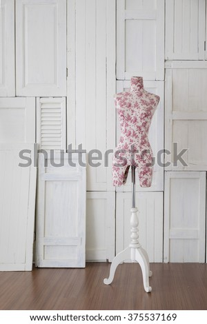 Mannequin with vintage pattern in the room with white wooden window wall - stock photo