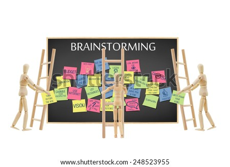 Mannequins holding (write down your goals and think outside the box) written on post it note climbing ladder to add to blackboard filled with Brainstorming ideas isolated on white background - stock photo