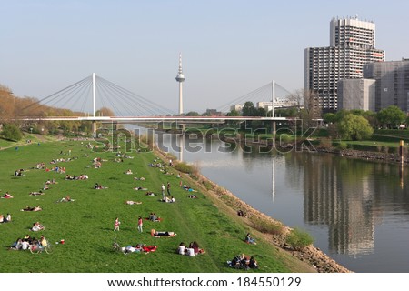 MANNHEIM, GERMANY - MAR 30, 2014: a sun-seeking crowd is relaxing at the waterfront grassland of Neckar river, enjoying the first warm and pleasant weekend of spring season - stock photo