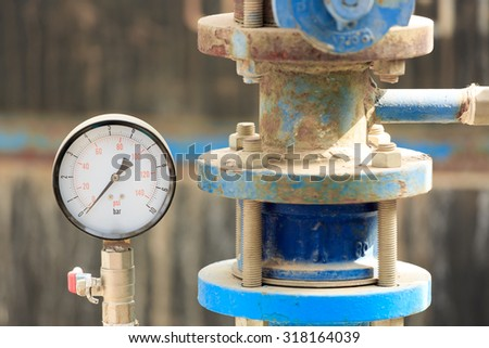 Manometer near old pipe on chemical plant - stock photo