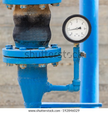 Manometer with blue pipe on chemical plant - stock photo
