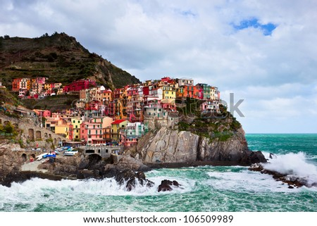 Manorola in Cinque Terre along the north western Italian Coast stands colorful and firm atop the cliffs as waves from a late winter storm to their best to reach the buildings. - stock photo