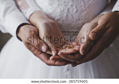 Mans and female hands hold wedding rings. - stock photo