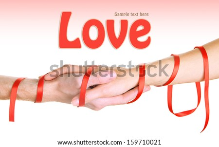 Mans and girls hands tied with ribbon on light background - stock photo