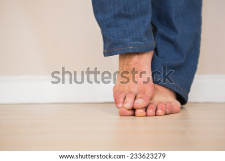 Mans bare feet on wooden floor at home in the living room