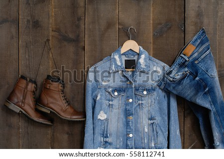 Mans boots, shoes and blue jeans shirt on wood background