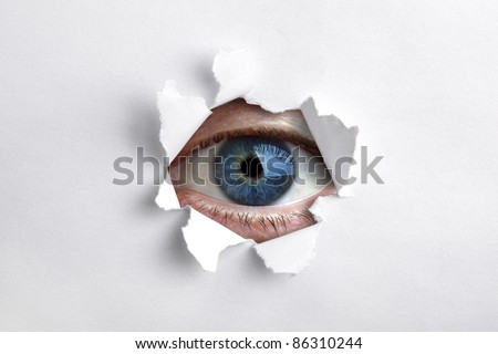 Mans eye peeking through a hole in white paper - stock photo
