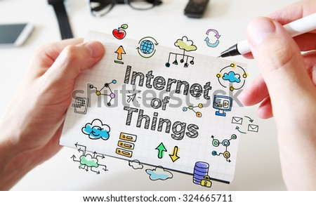 Mans hand drawing Internet Of Things concept on white notebook - stock photo