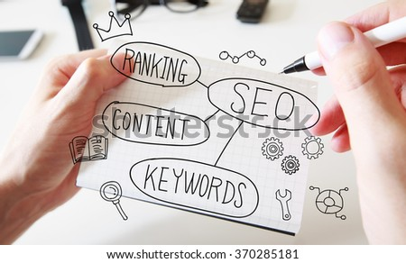 Mans hand drawing SEO concept on white notebook  - stock photo
