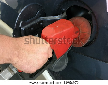Mans Hand Filling His SUV With Gasoline - stock photo